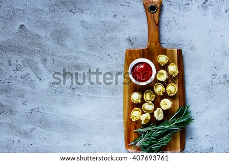 Top view of wooden cutting board with homemade raw Italian tortellini, tomato sauce and rosemary over concrete textured background, place for text, border. - stock photo