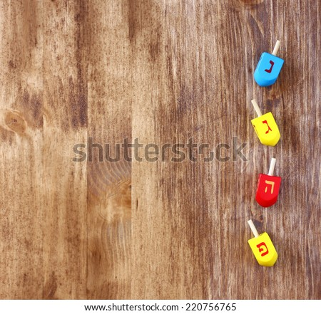 top view of wooden dreidels (spinning top) for hanukkah jewish holiday over wodden table - stock photo