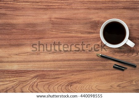 Top view of wooden office desk table with cup of coffee and pen. Copy space is available. Flat lay. - stock photo