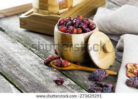 Top view of wooden pots with spoon and dried berries on old wooden background - stock photo