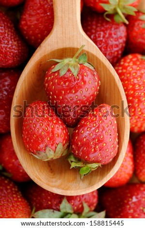 Top view of wooden spoon with some ripe strawberries - stock photo