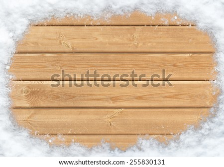 Top view of wooden surface covered with snow of the shape of a circle - stock photo