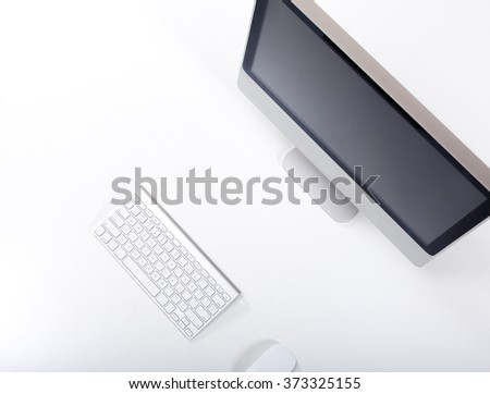 Top View of Working Place of Designer with large Computer Monitor Keyboard and cropped Mouse on White Desk black Screen - stock photo