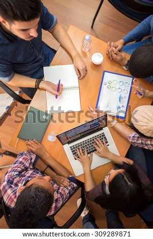 Top view of working table with students working in team  - stock photo