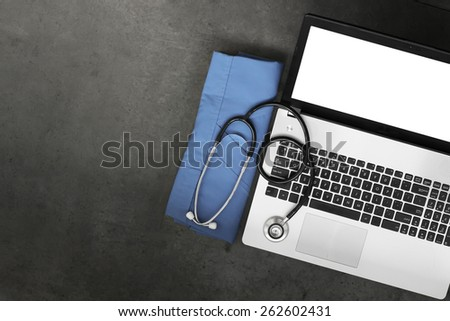 top view of workspace of medical with stethoscope and blue coat and blank screen computer laptop on texture desk background - stock photo