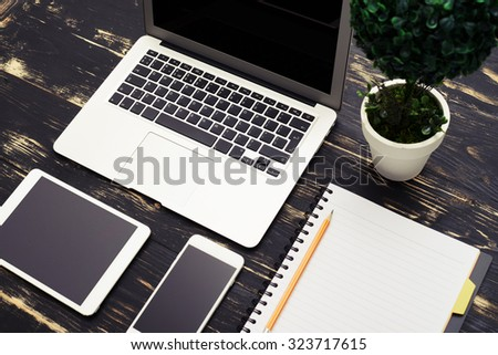 top view of workspace with laptop, smartphone, tablet pc and empty notebook - stock photo