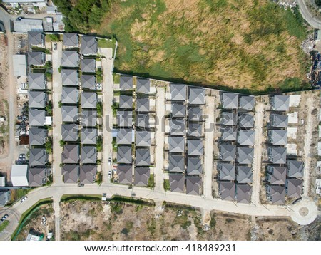 Top view of yards and cars along suburban street in Thailand - stock photo