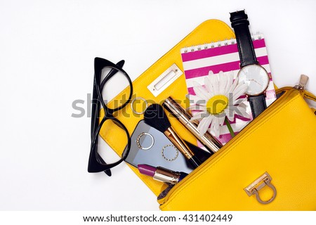 Top view of yellow bag with make up female fashion accessories. Stylish glasses, watch , lipstick , notebook , mascara , smart phone - stock photo