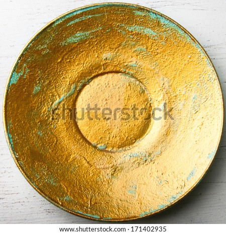 Top view of yellow painted decorative plate on the white wooden surface  - stock photo