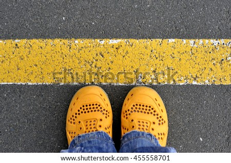 Top View of yellow shoes on the asphalt road with yellow line.