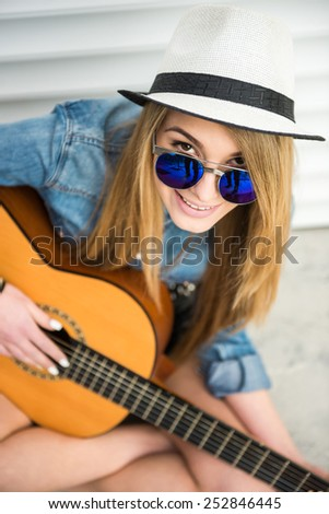 Top view of young beautiful, trendy girl with acoustic guitar is playing sitting on the floor. - stock photo