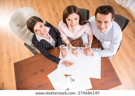 Top view of young couple and female realtor are sitting at the table with plan oh the house. - stock photo