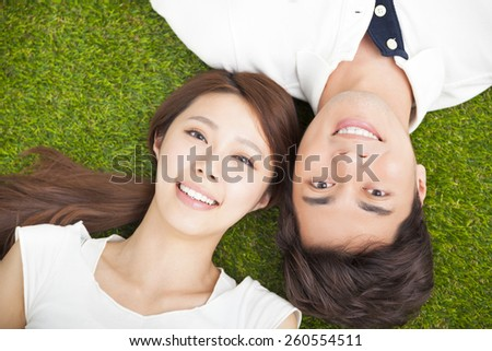 Top view of young couple  lying together on the grass - stock photo