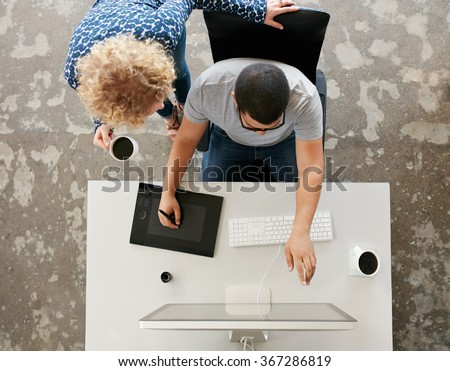 Top view of young graphic designers working in office. Using digitized graphic tablet, digitized pen and desktop computer. Man showing his work on monitor to woman standing by with a cup of coffee. - stock photo
