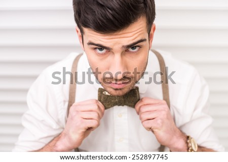 Top view of young, handsome man with suspenders and bow-tie. - stock photo