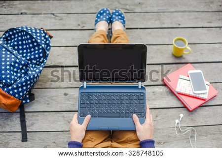 Top view of young hipster girl using laptop outdoors  - stock photo