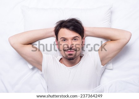 Top view of young man is lying in the bed. - stock photo