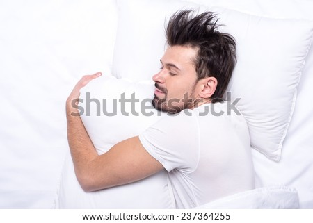 Top view of young man is sleeping in the bed. - stock photo
