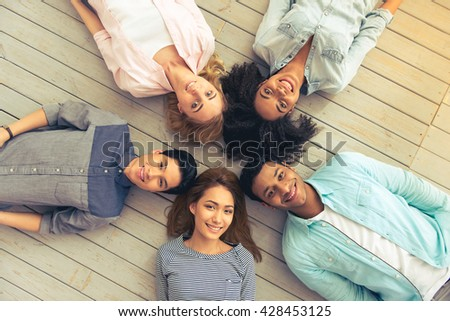 Top view of young people of different nationalities looking at camera and smiling while lying on the floor - stock photo