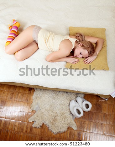 Top view of young pretty woman in lingerie and knee-high stockings asleep on bed - stock photo