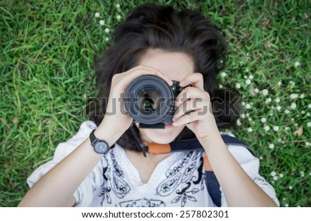 Top view of young woman lying on grass ground with hand holding camera, focus on lens. - stock photo