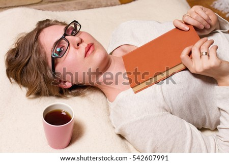top view of young woman reading book and drinking coffee or tea