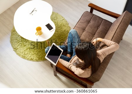 Top view of young woman reading on tablet pc at home - stock photo