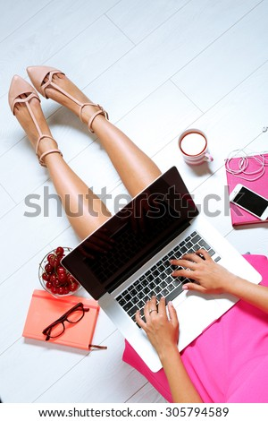 Top view of young woman sitting on floor with laptop - stock photo