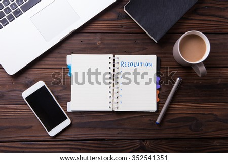 Top view office desk mockup: laptop, notebook, smartphone, and cup of coffee on rustic brown wooden background. New year resolution 2016