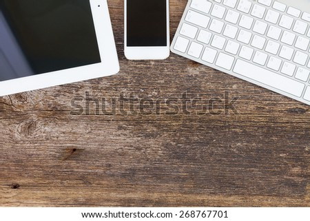 Top view office workplace -  tablet, keyboard and phone on wooden background with copy space - stock photo