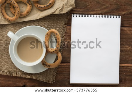 Top view office workplace: white notepad with bagels and coffee on the wooden table.