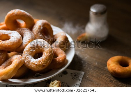 Top view on a detail of bunch of fresh homemade donuts (doughnuts) on a white plate, with sugar bowl, rolling pin on a dark wooden floor with free copy space for your text - stock photo