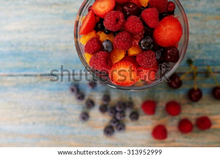 Top view on a vintage wooden desk with peeling paint, there is a deep glass bowl with fresh chopped salad of ripe berries - stock photo