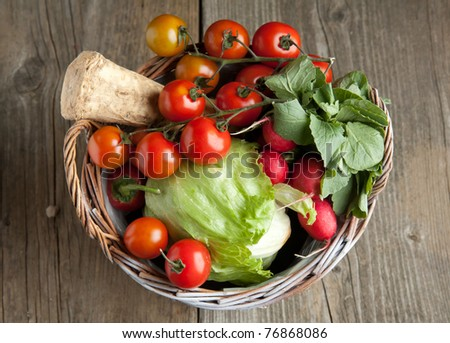 Top view on basket with fresh red paprika, tomato, radish and green salad - stock photo