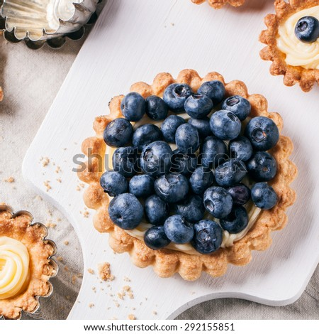 Top view on blueberry mini tart served on white cutting board with vintage teaspoons. Square image - stock photo