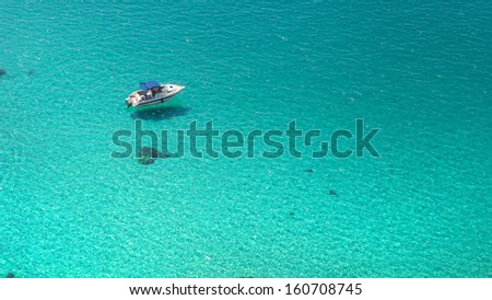 Top view on boat in azure clear water - stock photo