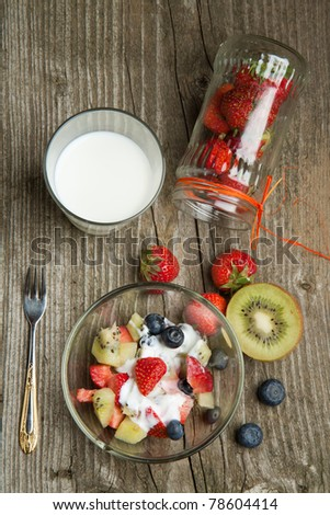 Top view on bowl of fruit salad with fresh strawberries, blueberries and kiwi with glass of milk on old wooden table table - stock photo