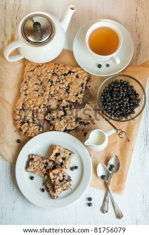 Top view on breakfast with homemade blueberry pie, bowl of fresh blueberries and white cup of tea - stock photo