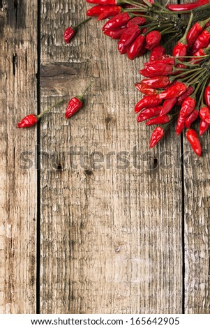 Top view on bunch of red hot chili peppers over old wooden background - stock photo