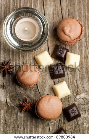 Top view on chokolate macaroons with pieces of white and black chocolate and lightning candle on old wooden table - stock photo