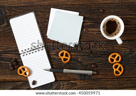 Top view on cup of coffee and notepad on a wooden background. Space for your text