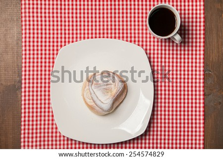 Top view on cup of coffee and sweet cupcake with white chocolate. On checkered napkin - stock photo