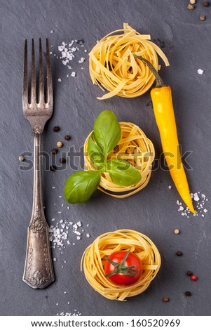 Top view on dry pasta, fresh tomato, basil and yellow chili pepper served with sea salt and vintage fork on dark gray background - stock photo