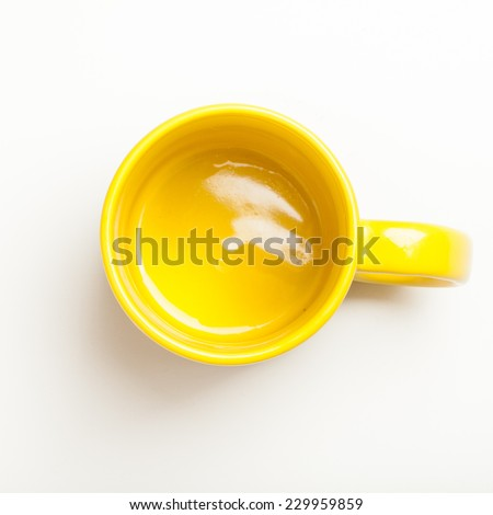 Top view on empty yellow coffee or tea mug or cup. Studio shot from above on white background.