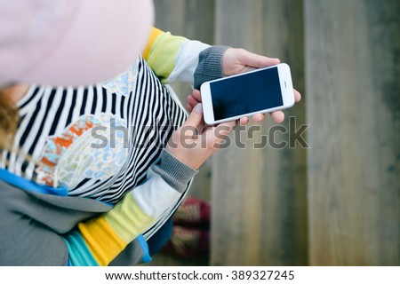 Top view on female with smart phone on stairs. Mobile life on the go  - stock photo