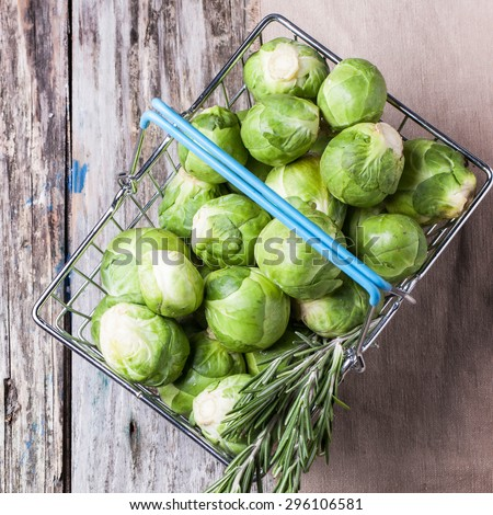 Top view on food basket of brussels sprouts and rosemary on old wooden table. Square image - stock photo