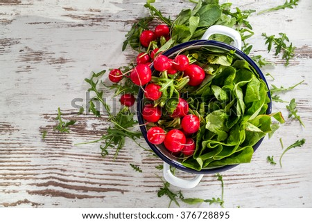 Top view on fresh wet radishes in white colander over old wooden table - stock photo
