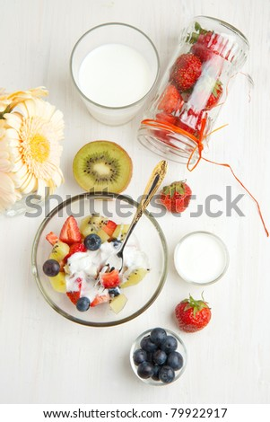 Top view on glass bowl of fruit salad with fresh strawberries, blueberries, kiwi and whipped cream, with bunch of flowers and glass jar of strawberries on white table - stock photo
