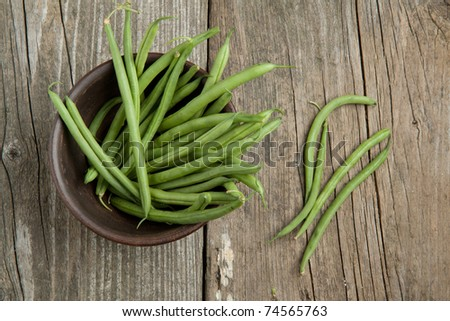 Top view on green beans in ceramic bowl on old wooden table - stock photo