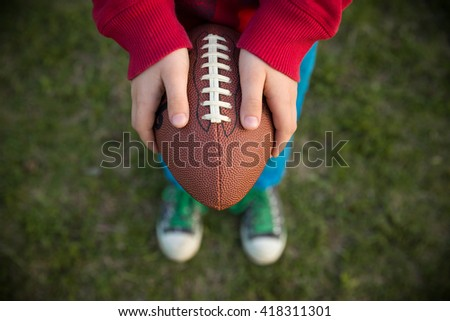 Top view on hands of little kid boy holding football on the stadium on a sunny day. Child  ready to throw a football. Sport concept. Sport activities for children outdoors. - stock photo